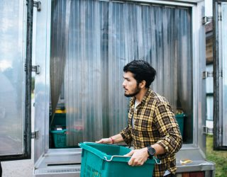 Portrait of a hipster farmer holding box of fruit lift up to the car to go market for sell.